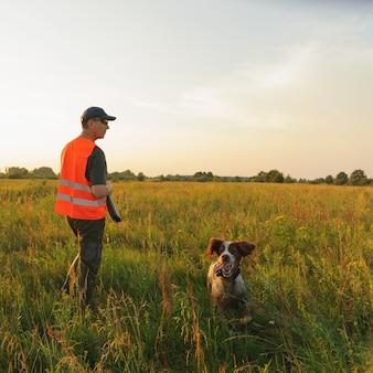 Caçador na temporada de caça ao outono com seu cão de caça no pôr do sol.