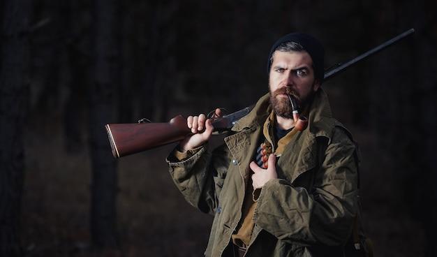 Caçador severo e brutal de barbudo com chapéu preto, jaqueta cáqui e manto comprido segura uma arma no ombro e fuma um cachimbo
