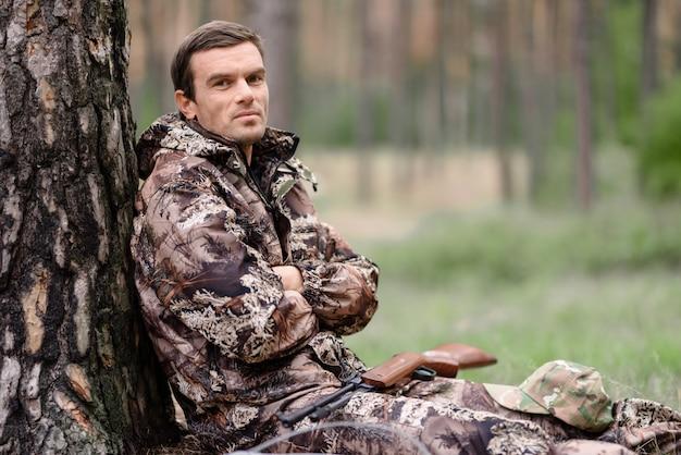 Caçador solitário em camo tem descanso sentado debaixo da árvore