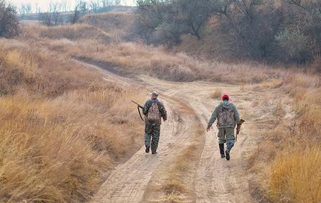 Caçadores andando com espingardas ao longo da estrada em busca de presas