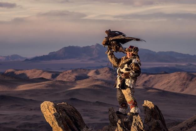 Caçadores de águia da mongólia em trajes tradicionais de raposa da mongólia