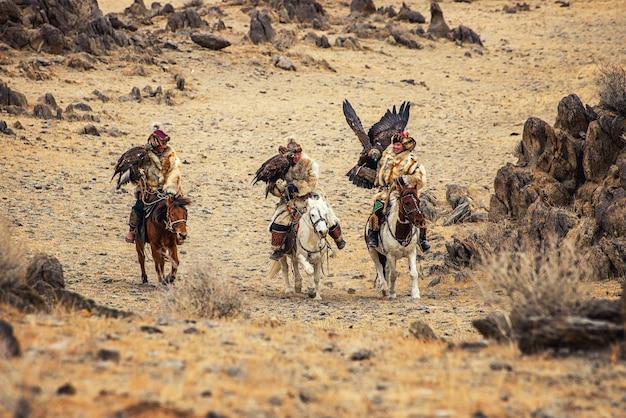 Caçadores de águia do cazaquistão em trajes tradicionais da mongólia