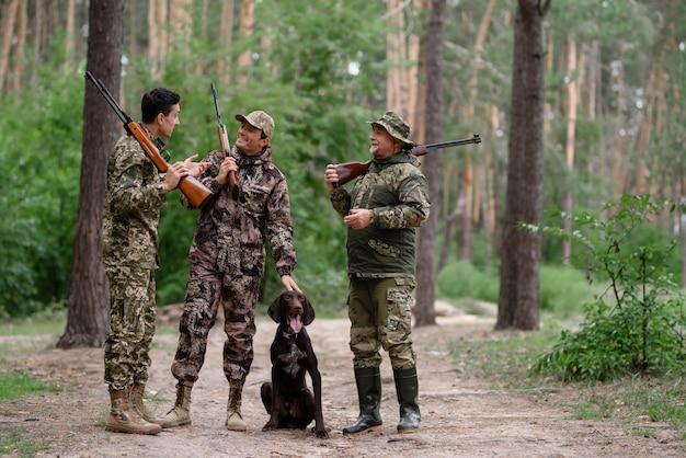 Caçadores falando e rindo entre pinheiros.