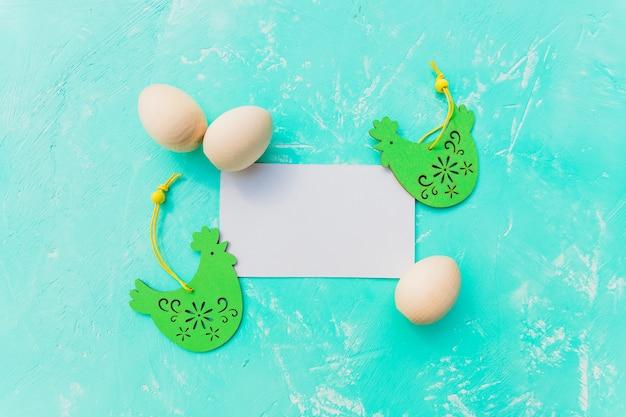 Caçar convite com ovos e frango de madeira sobre fundo azul e placa vazia branca