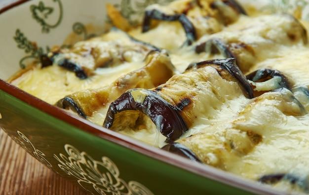 Caçarola com queijo de berinjela com queijo, carregada com berinjela fresca, espinafre e tomate assado no fogo