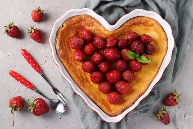 Caçarola de coalhada em forma de coração decorada com morangos, vista de cima