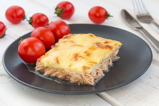 Caçarola de peixe assado com queijo na mesa de madeira branca
