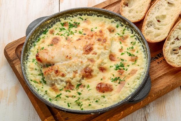 Caçarola de peixe branco com queijo, creme de leite e cebola em uma mesa de madeira