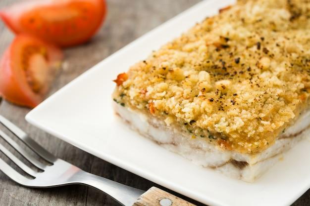 Caçarola de peixe branco com queijo em madeira.