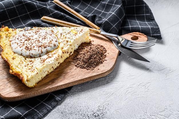 Caçarola de queijo cottage com chocolate em uma placa de corte. fundo branco. vista do topo. copie o espaço.