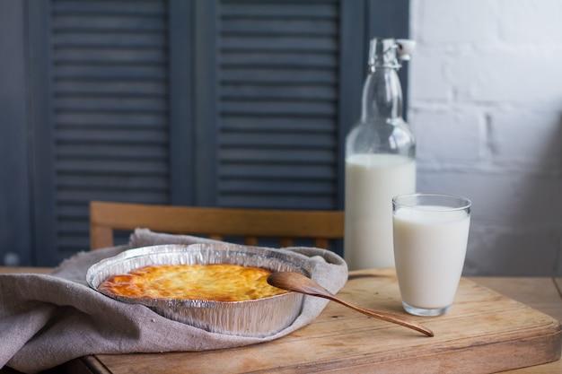 Caçarola de queijo cottage com copo e garrafa de leite no fundo da mesa de madeira. caçarola de queijo cottage.