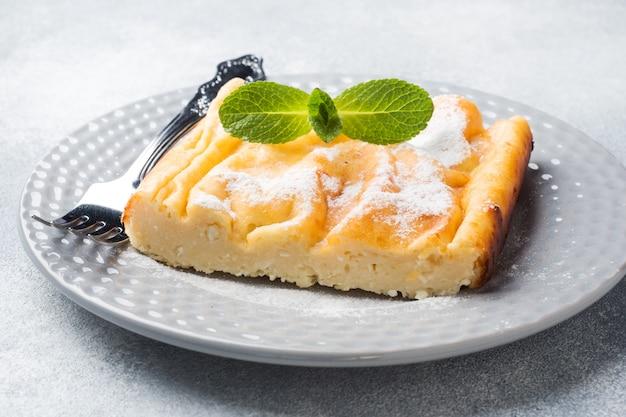 Caçarola de queijo cottage em um prato com açúcar em pó e folhas de hortelã.