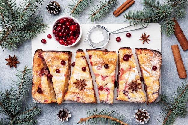 Caçarola de torta de queijo cottage com cranberries e especiarias polvilhadas com açúcar de confeiteiro em um carrinho de madeira. mesa de concreto cinza.