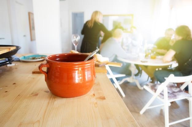 Caçarola na mesa e pessoas sentadas e comendo comida perto da janela depois da aula de culinária