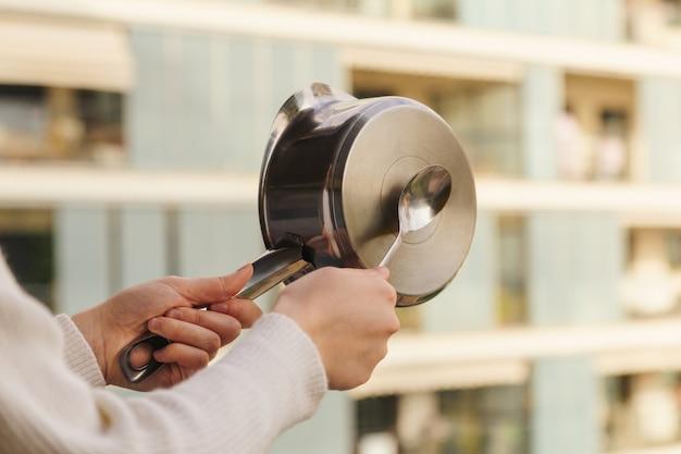 Caçarola protesta da sacada contra as medidas do governo, fazendo barulho atingindo a panela
