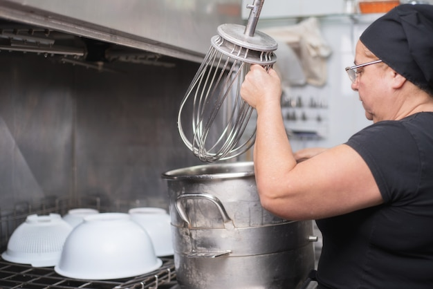 Caçarolas do carregamento do empregado de mulher em uma máquina de lavar louça industrial no restaurante.