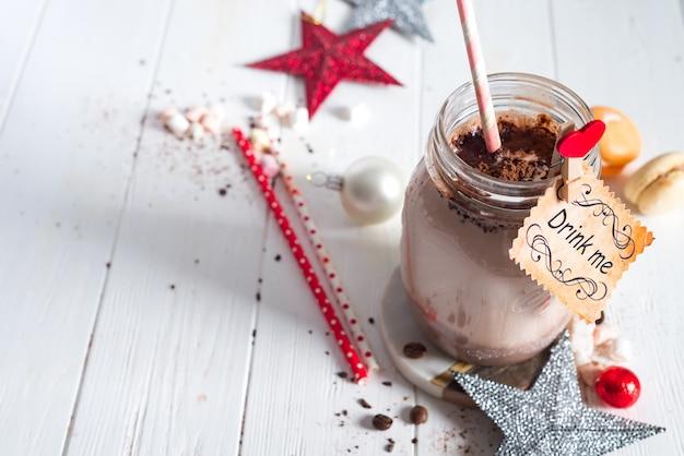 Cacau com marshmallow e palhas no pote de vidro decorado com estrelas de natal