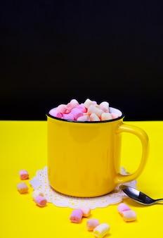 Cacau com marshmallow em uma caneca amarela, ao lado de uma colher de ferro