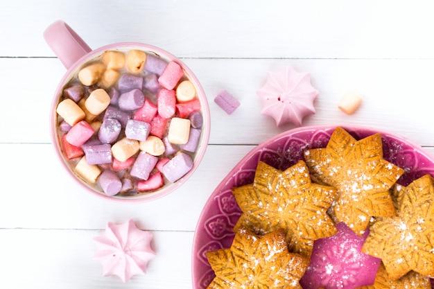 Cacau com marshmallow em uma xícara rosa e biscoito de gengibre
