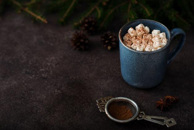 Cacau de natal com marshmallows em uma caneca, árvore de natal, cópia do espaço
