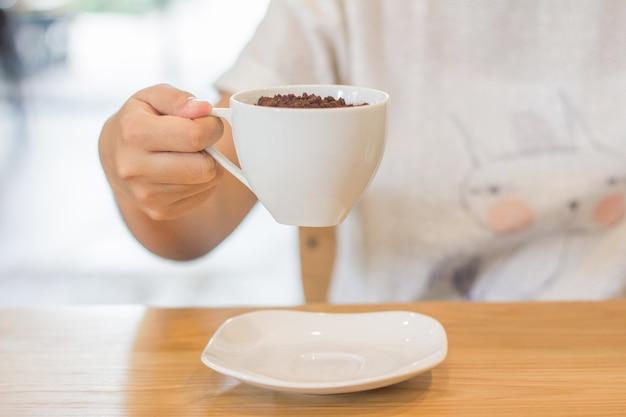 Cacau em pó e copo branco na mão das mulheres na loja de café