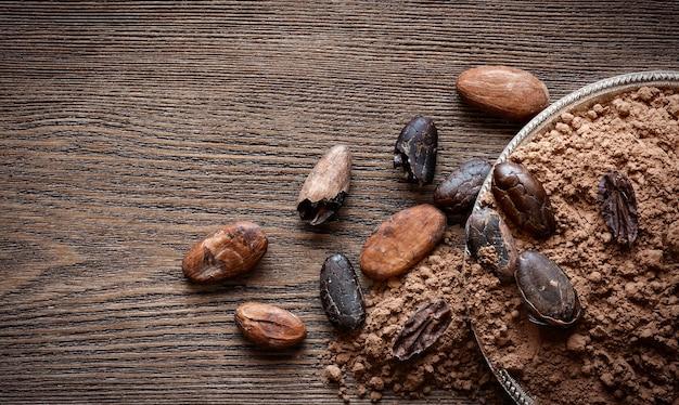 Cacau em pó e grãos de cacau em fundo de madeira