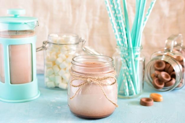 Cacau em uma jarra. bule de café, marshmallows e tubos de coquetel azuis em um borrão.