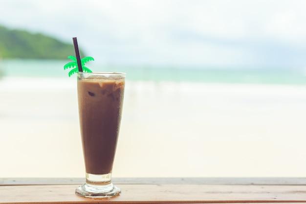 Cacau frio em um copo sobre uma mesa de madeira à beira-mar no verão