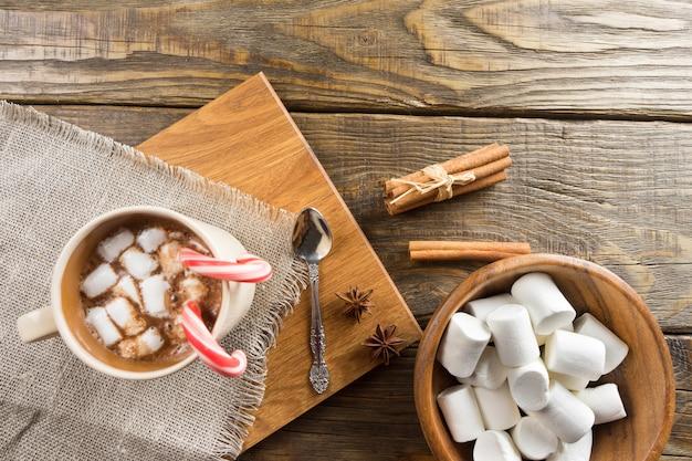 Cacau, marshmallow e canela na mesa rústica.