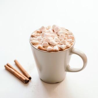 Cacau quente com marshmallow e canela doces na tabela branca.