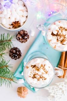 Cacau quente com marshmallow e canela em pó em copos em cima da mesa em decorações de natal, vista superior
