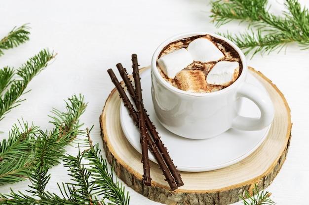 Cacau quente com marshmallows decorados ramos de pinheiro em madeira branca
