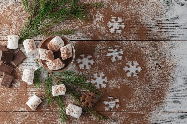 Cacau quente de inverno com marshmallows, calda de chocolate, flocos de neve de açúcar em um copo alto