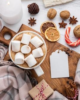 Cacau quente e marshmallows em xícara com vela e frutas cítricas secas