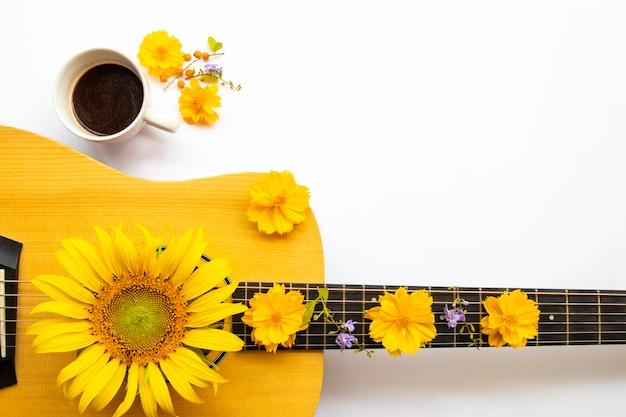 Cacau quente, guitarra e cosmos de flores amarelas, girassóis do estilo de vida