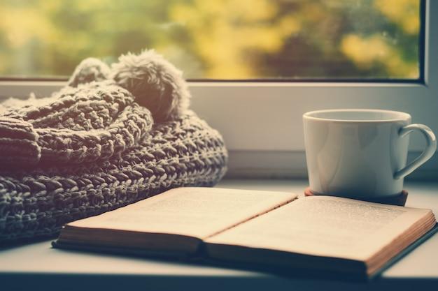 Cachecol de lã, uma xícara de chá e livro no peitoril da janela. hygge e aconchegante conceito de outono