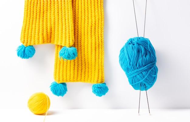 Cachecol de malha amarelo, ao lado de fios azuis e amarelos sobre fundo branco.