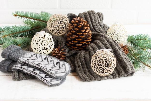 Cachecol de malha quente e luvas na composição com bolas perfuradas, cones e ramos de abeto em um fundo branco. o conceito aconchegante de natal.