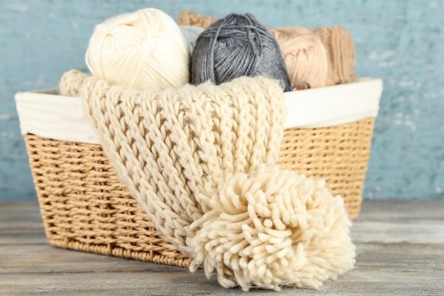Cachecol de tricô e fios na cesta, com fundo de madeira