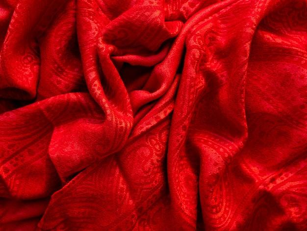 Cachecol vermelho brilhante. acessório quente dobrado. fundo de têxteis.