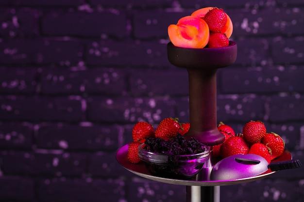 Cachimbo de água com sabor de morango close-up em fundo escuro, objetos