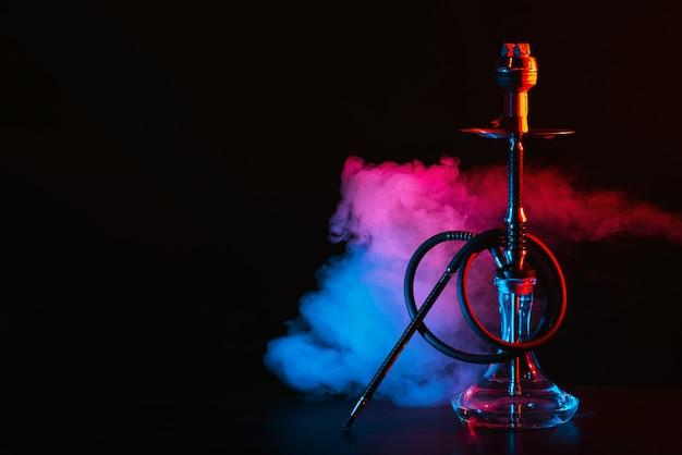 Cachimbo de água com um balão de vidro e uma tigela de metal shisha com fumaça colorida em cima da mesa