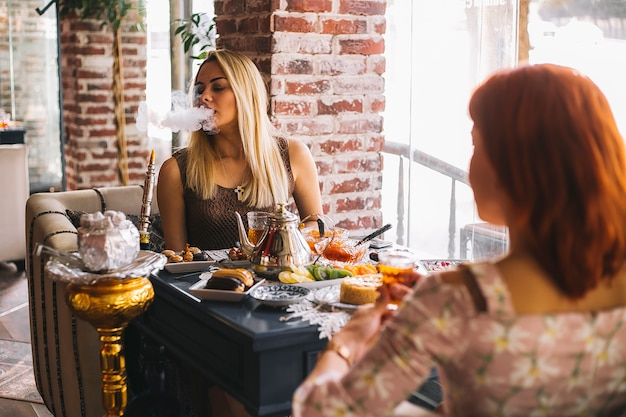 Cachimbo de água de fumar mulher no restaurante