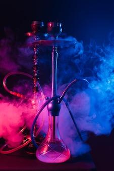 Cachimbo de água elegante com uma nuvem de fumaça em um fundo preto com brilho vermelho e azul