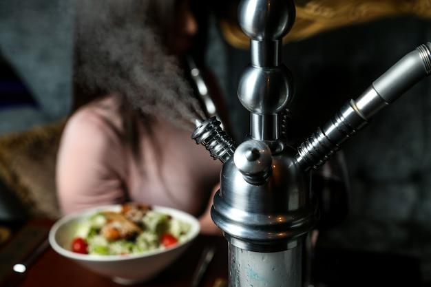 Cachimbo de água enquanto fuma na vista de perto da mesa
