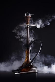 Cachimbo de água na moda com nuvem de fumaça em fundo preto