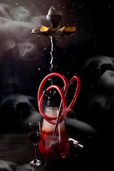 Cachimbo de água vermelho com frutas sobre um fundo preto com fumaça