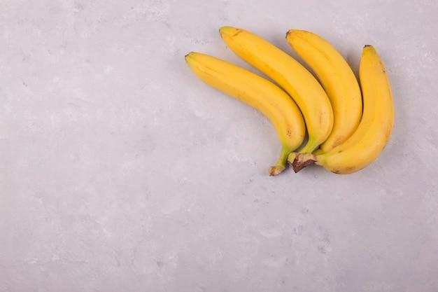 Cacho de bananas amarelas isoladas em concreto no canto superior