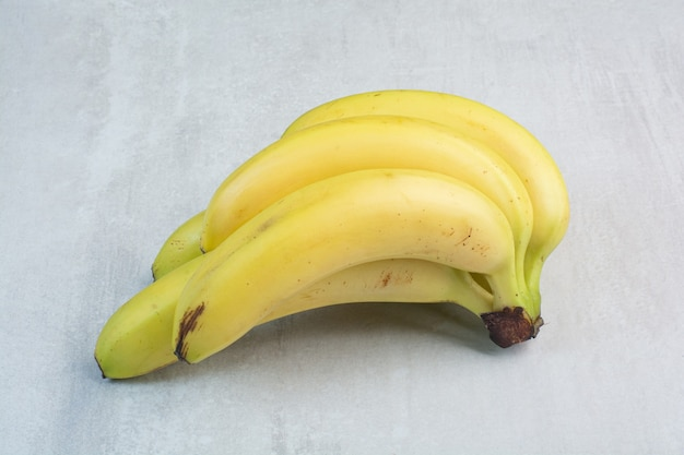 Cacho de bananas em fundo de pedra