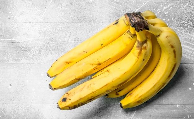 Cacho de bananas frescas. sobre fundo branco rústico.